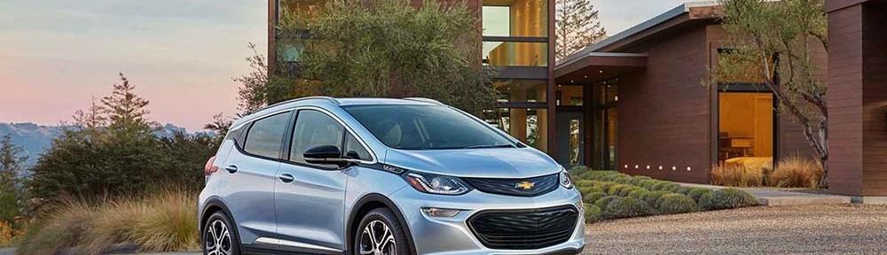 2017 Chevrolet Bolt by a modern home