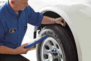 Chevy Service Technician Measuring Tire Tread Depth
