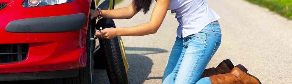 Changing a flat tire on the side of the road