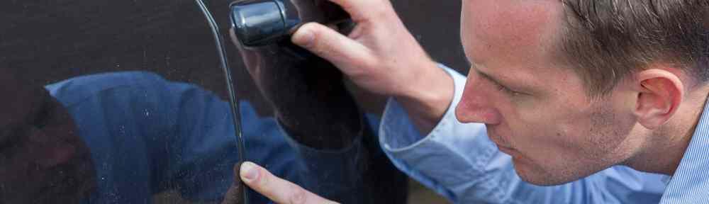 man inspects scratch on car door panel